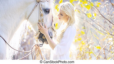 Attractive blonde cutie touching royal horse - Attractive...