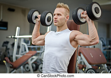 Attractive young man training with dumbbells in gym
