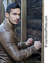 Handsome young man pressing fists on wood planks wall and...