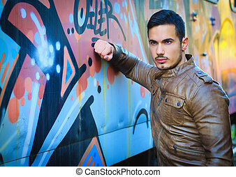 Handsome young man next to graffiti covered wall