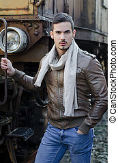 Attractive young man in leather jacket and jeans next to old...