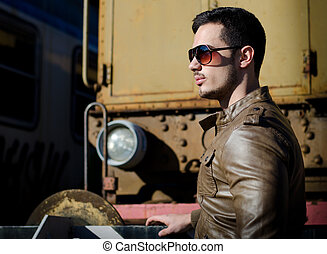 Attractive young man in leather jacket and jeans next to old train