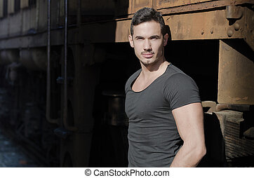 Handsome young man in dark t-shirt in front of old train -...