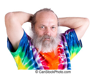 Senior male adult man holding his hair on the back casually and looking at you in his tie dye T-shirt