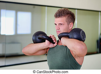 Handsome young man working out in gym with kettlebells -...