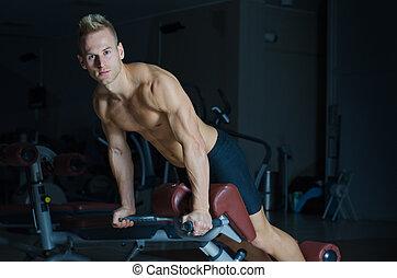 Shirtless young man exercising femural biceps on gym equipment