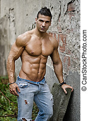 Muscular young latino man shirtless in jeans leaning on wall...