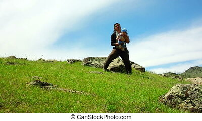 Mongolian Father lifting his daughter at grassland