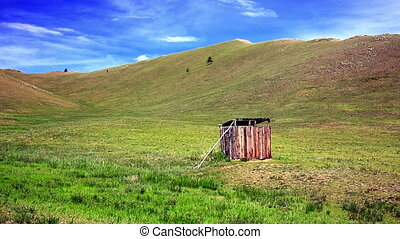 Mongolian wooden squat toilet outside home, grassland of...