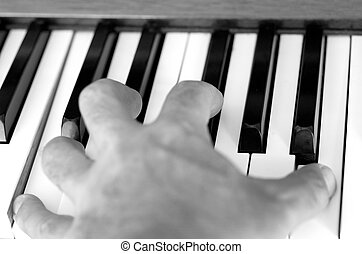 Piano player hand plays the piano. (BW).