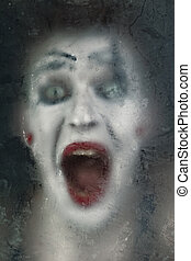 Scary face screaming mime for murky glass closeup