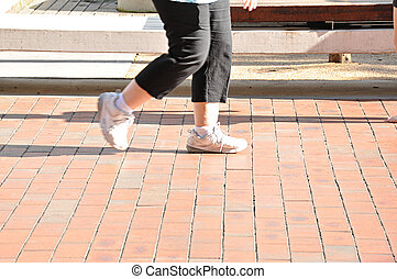 Legs of woman walking slowly on the footpath - Legs of fat...