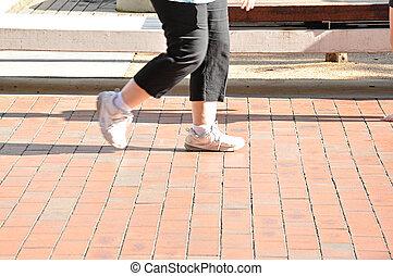 Legs of woman walking slowly on the footpath - Legs of fat...