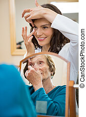 Eyecare Doctor Teaching Senior Woman To Insert Contact Lens...