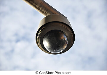 Black round shape CCTV - Surveillance camera on cloudy sky...