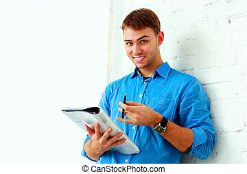Young happy student standing with folder near the wall