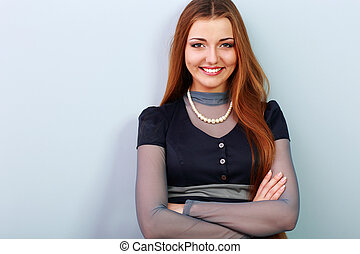 Young beautiful happy woman with arms folded on gray...