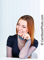 Young beautiful laughing woman looking right isolated on a white background