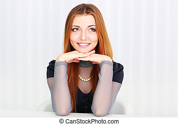 Portrait of a beautiful woman sitting at the table and looking up at copyspace