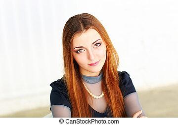 Young beautiful pensive woman looking at camera