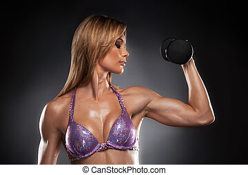 Beautiful fit woman doing fitness. Left hand with dumbbells...