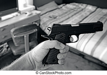 Young man hand holds a 9mm gun in his bedroom