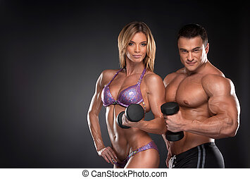 Couple of well trained bodybuilder with dumbbells. Woman and...