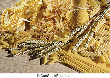 pasta - variety of uncooked pasta on wooden table with ears...