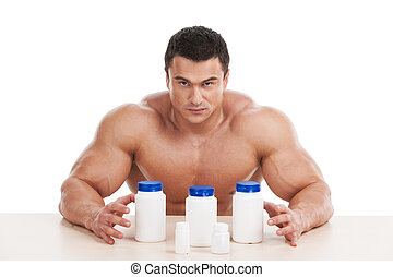 Muscular handsome bodybuilder with pills and dope. Sitting...