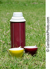 Thermos - Tmetal thermos with two cups during picnic...