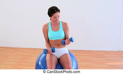 Fit brunette sitting on an exercise ball and lifting weights...