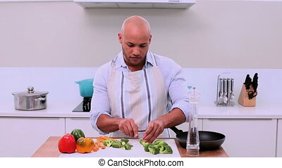 Handsome man preparing vegetables and showing thumb up in...