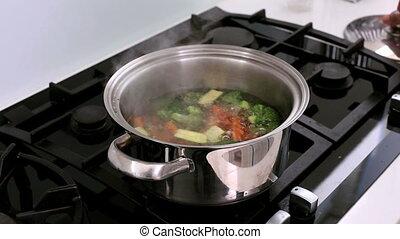 Handsome man smelling boiling vegetables
