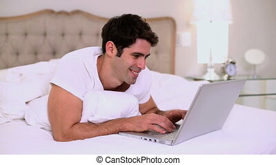 Smiling handsome man using laptop in bed in bright bedroom