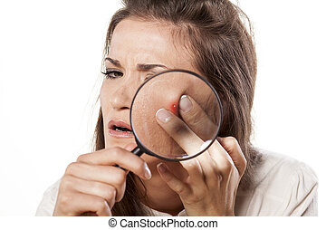 self cosmetics - girl squeezing her pimples using magnifying...