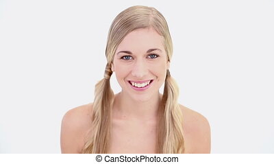 Happy nude blonde using tweezers on white backgroud