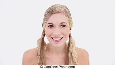 Happy nude blonde using powder brush on white background