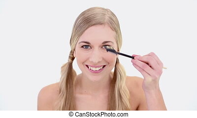 Happy nude blonde using eyebrow brush on white background