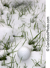 single dimpled golf ball in the snow covered grass - a lone...