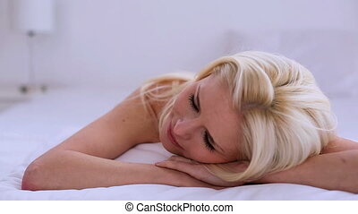 Beautiful blonde woman day dreaming while lying on her bed...