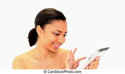 Gleeful dark haired woman using her white tablet on white...