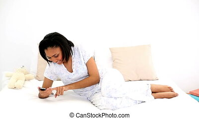 Dark haired woman messaging with her smartphone lying on her...