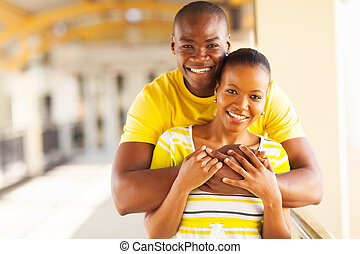 young african american couple hugging - portrait of young...