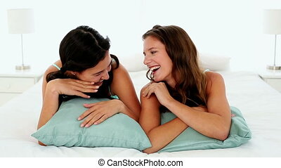 Attractive chatting women lying on bed in bright bedroom