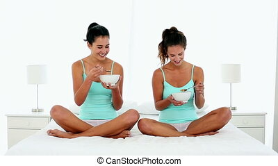 Content young women eating cereal sitting on bed in bright...