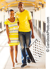 young african couple in shopping center - cheerful young...