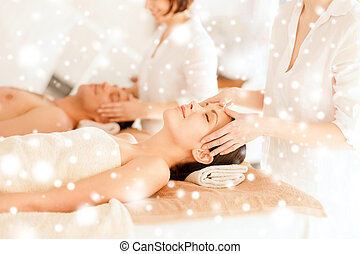 couple getting facial massage in spa