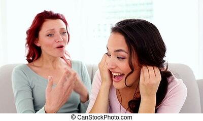 Two attractive women listening to headphones
