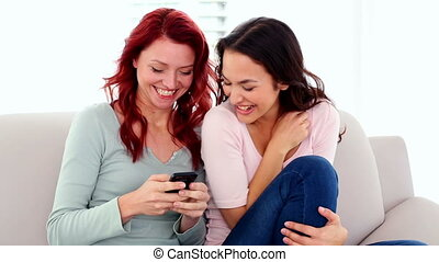 Surprised cute women using a smartphone while sitting on...