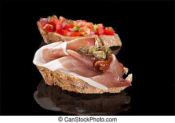 Delicious canape isolated on black. - Bruschetta and...